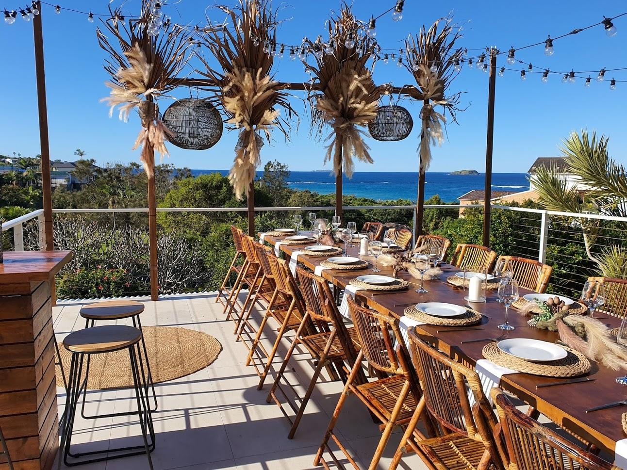 Festoon lighting dried botanical floral arrangements, bamboo chairs, timber topper tables