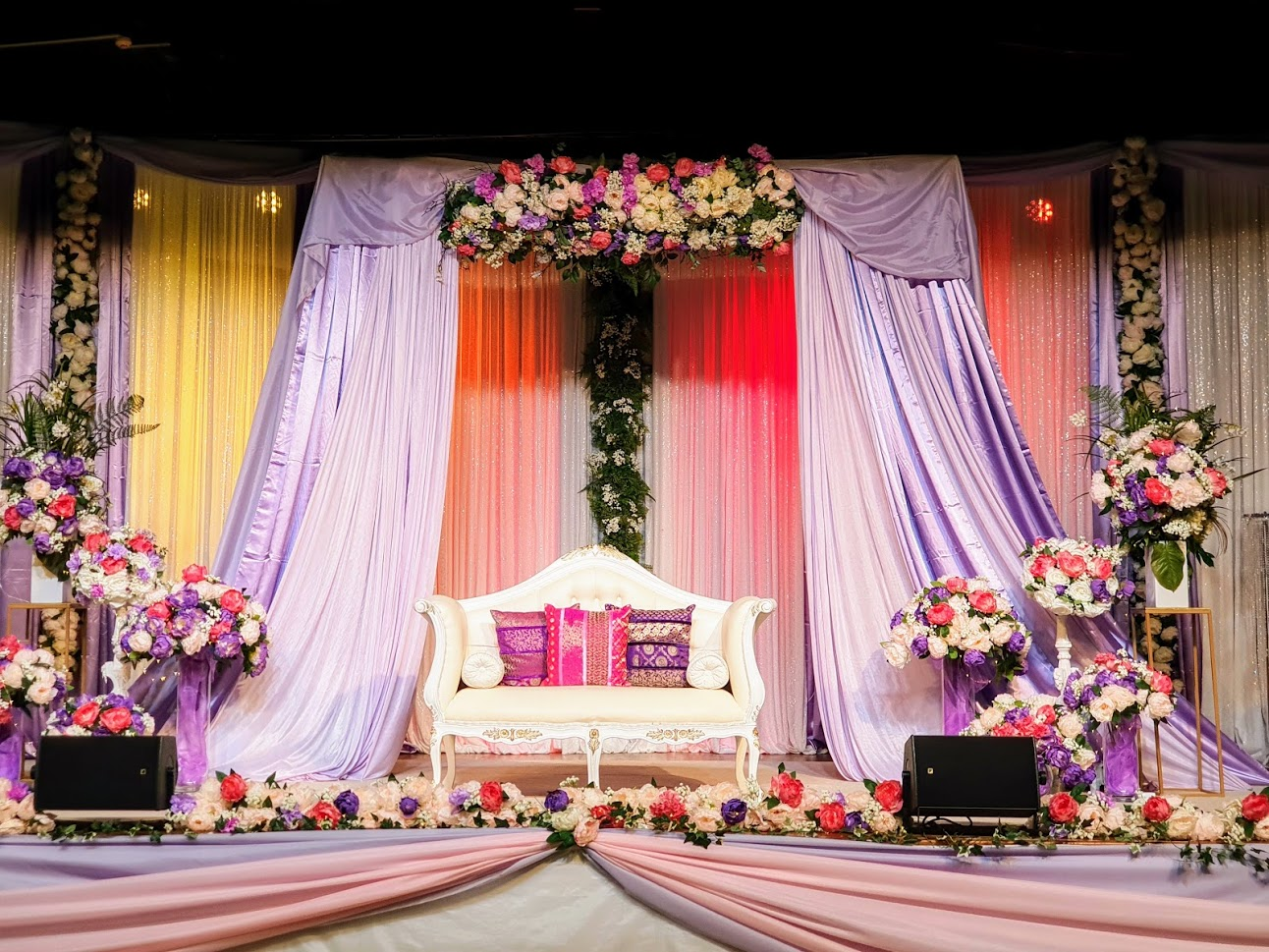 Indian Backdrop Stage lilac, white sequin, hot pink. pale pink, purple grouped floral arrangements