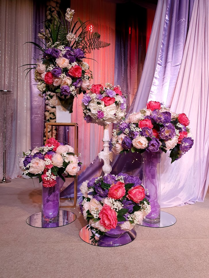 Stage decorations hot pink, pale pink. purple flowers in glass vases + pillars