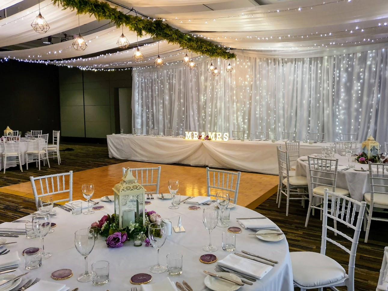 Jetty Harbour Rooms - Marquee ceiling canopy, greenery & wrought iron pendent lanterns spine, Tiffany chairs. daisy lanterns - Pacific Bay Resort
