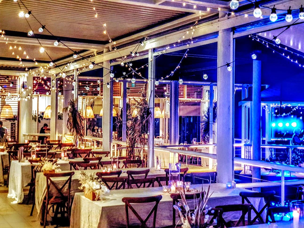 Festoon Fairy Lights Brown Hampton Chairs Bay side Restaurant