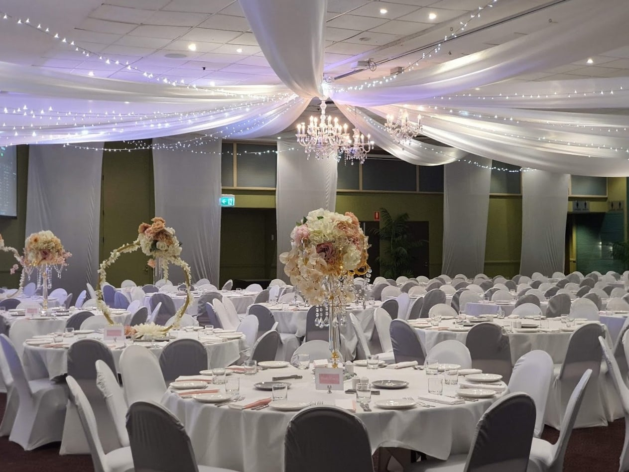 Star ceiling canopy white & fairy lights, crystal chandeliers, white chair covers, white silk wall drops