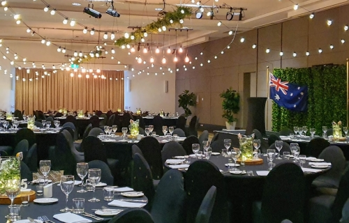 Jetty Harbour Marina Rooms - Marquee ceiling canopy, greenery & Festoon lights, Edison chandeliers, Black chair covers, Table decoration glass vase  battery fairy lights, eucalyptus, babies breath on a timber log- Pacific Bay Resort