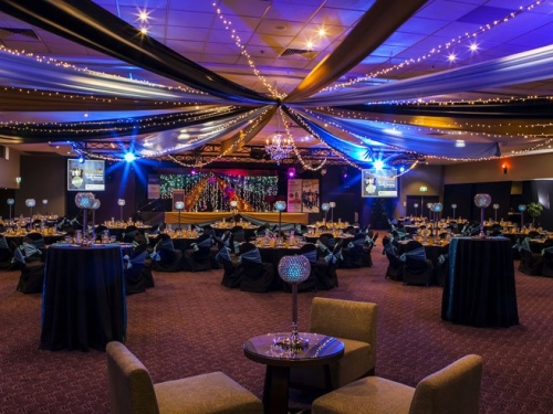 Star ceiling canopy black, gold & silver, crystal chandeliers, black chair covers aqua side tie sash  - Grand Auditorium Cex