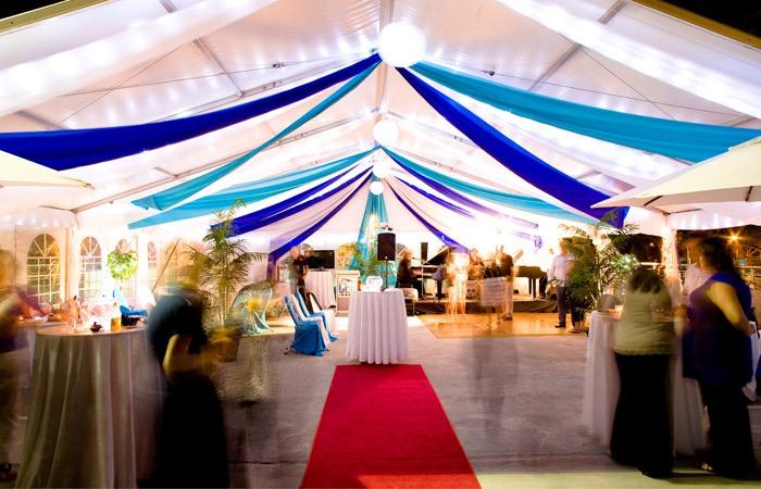 Marquee ceiling canopy aqua + royal blue silks + lanterns, red carpet