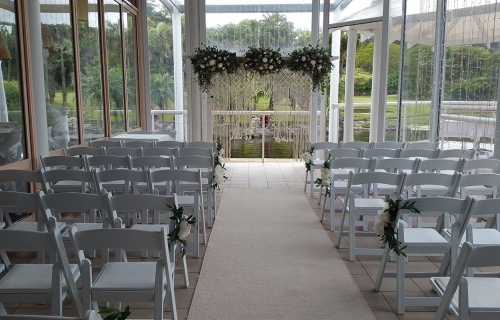 Wedding ceremony white timber arbour macramé rope fresh flowers Bay side lower deck Pacific Bay Resort