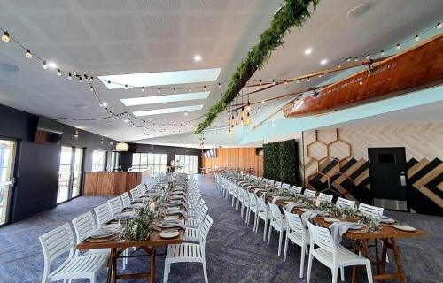 Woolgoolga surf  ceiling canopy, fern greenery ,festoon lighting. Edison chandeliers. photo booth greenery