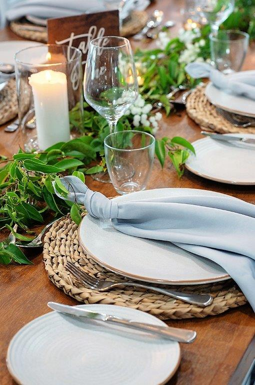 Woolgoolga surf  table décor fresh ficus + babies breath, dove grey knot napkins, rattan placemats, timber table numbers white writing, glass cylinder vase + fresh pillar candle, timber topper tables