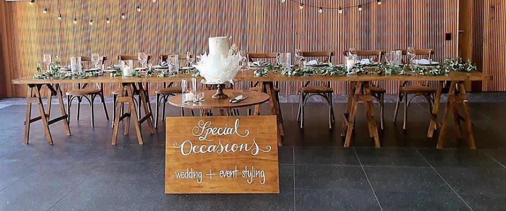 Woolgoolga surf  Bridal table décor ivy string, timber table topper + timber saw horses + cake table timber round 1m diameter + black wrought iron base